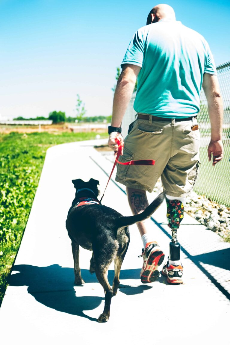 Amputee with service dog walking on sidewalk